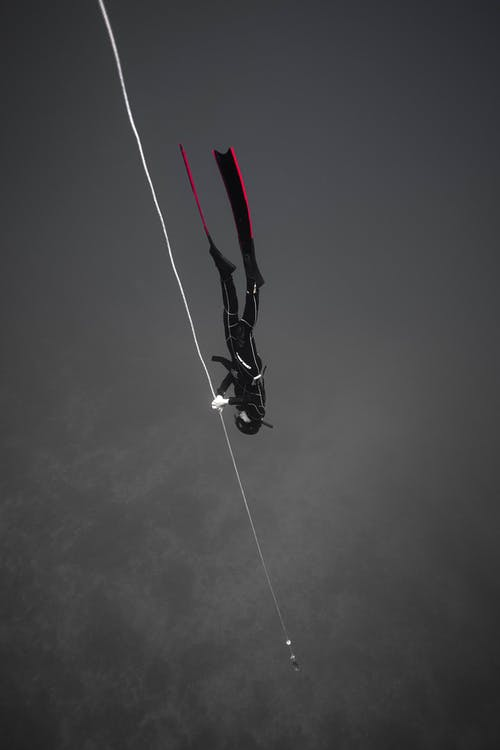 Person in Black and White Jacket and Black Pants Hanging on Rope