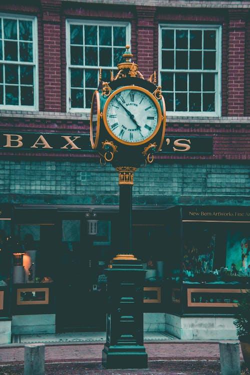 Round Yellow and Black Analog Pedestal Clock Displaying 4:58
