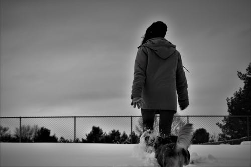Grayscale Photo Of Person Wearing Coat Walks On Snow