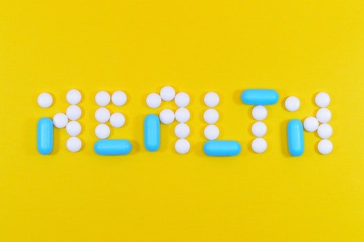 White and Blue Health Pill and Tablet Letter Cutout on Yellow Surface