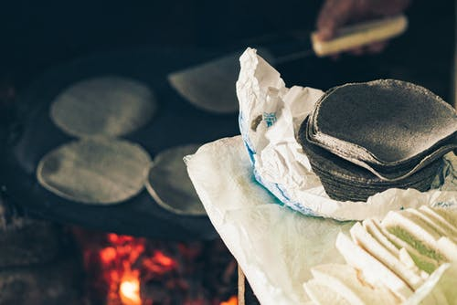 High angle of crop anonymous cook frying Mexican blue tortilla on fireplace near table with homemade cheese