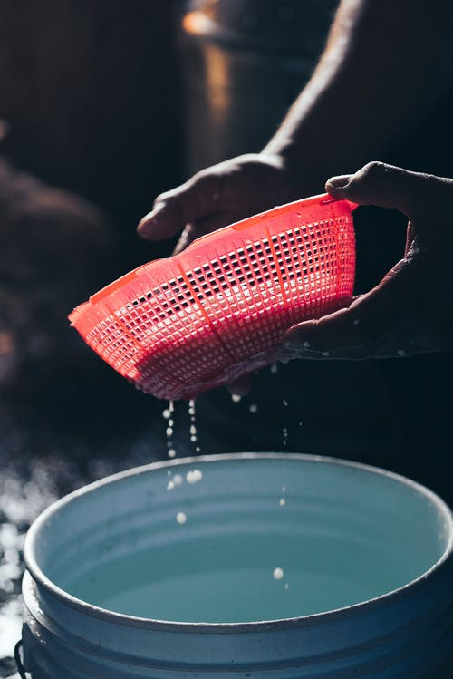 Person squeezing cottage cheese in colander