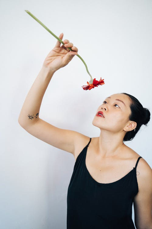 Woman in Black Tank Top Holding a Red Daisy