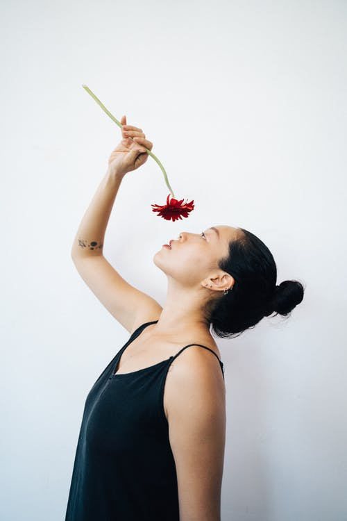 Woman in Black Tank Top Holding a Red Daisy Flower