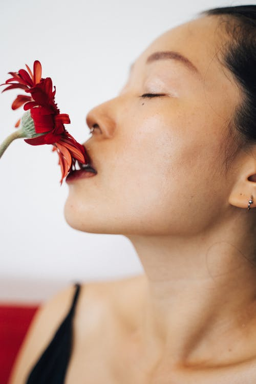 Woman Smelling a Red Flower