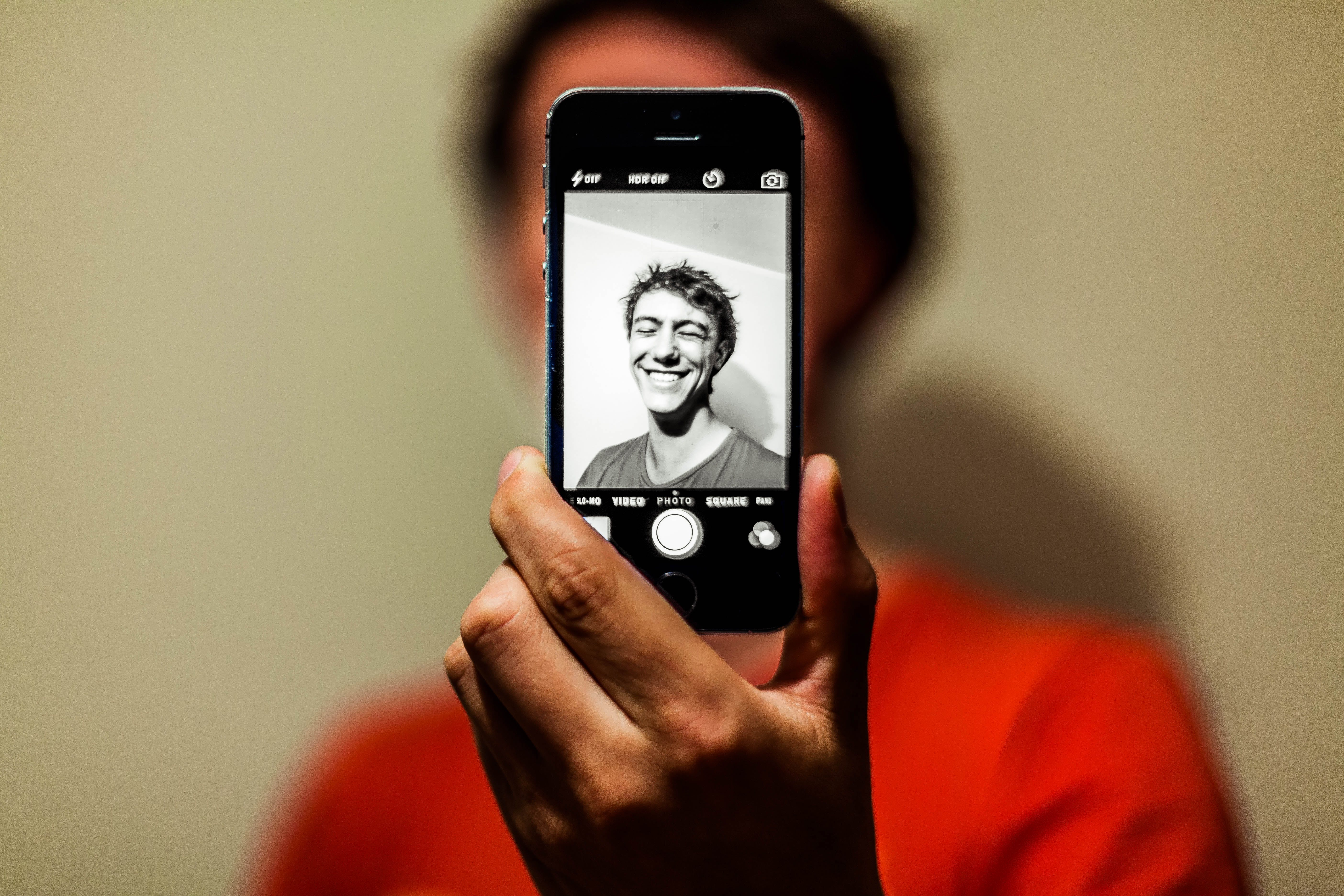 Man in Red Shirt Having Selfie on His Iphone in Grayscale Mode