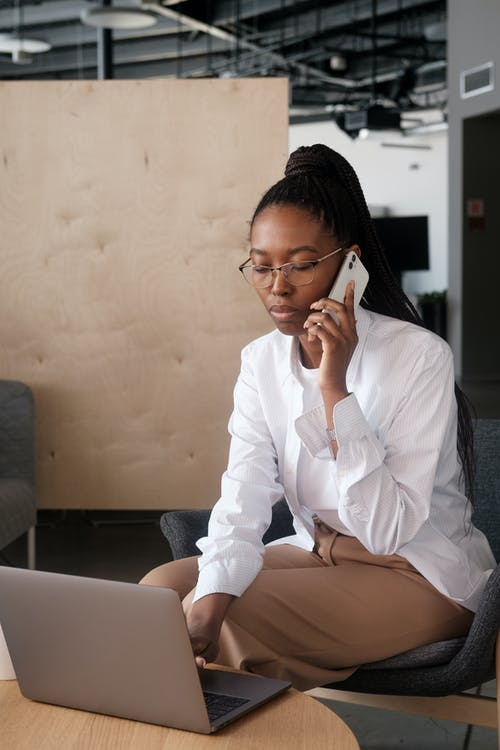 Black woman in smart casual clothes answering phone call and browsing data on netbook in workplace