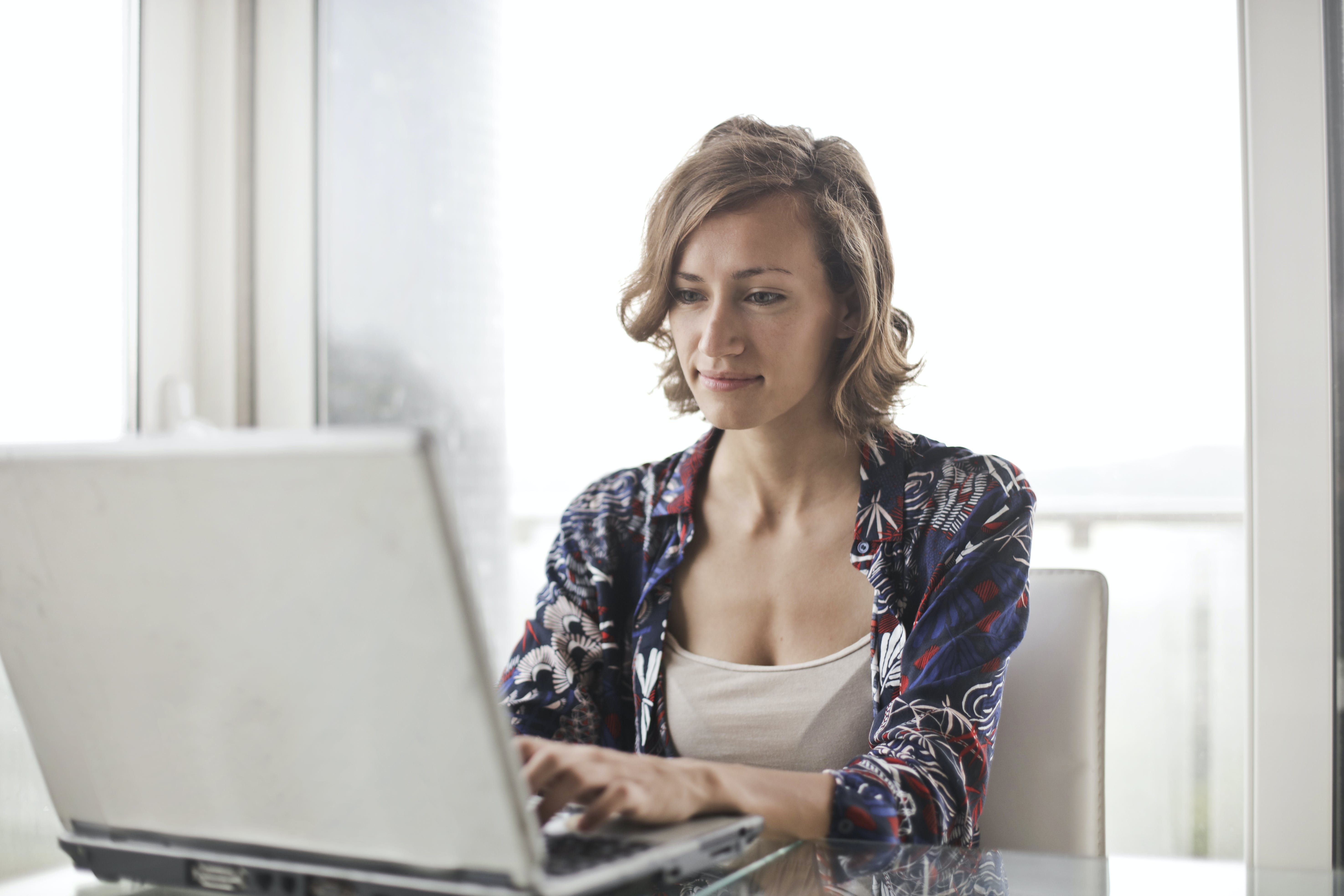 Woman in Blue Floral Top Sitting While Using Laptop