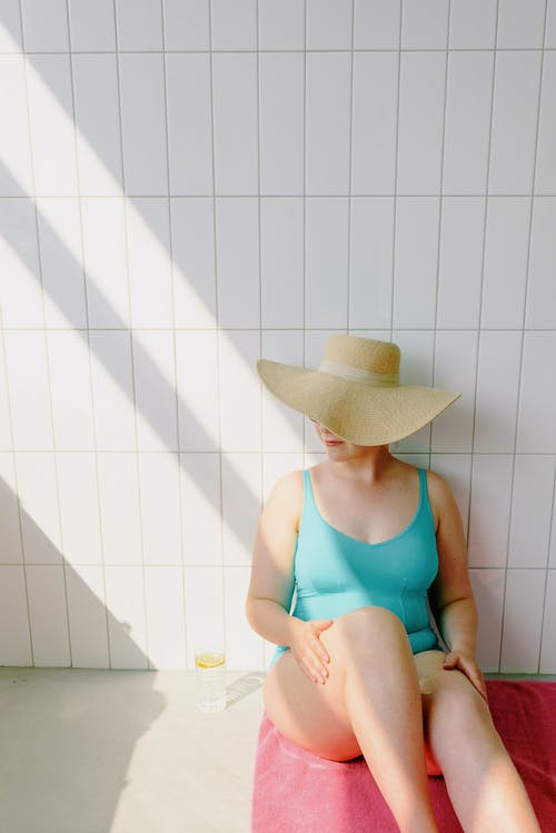 Woman in Teal Swimsuit Sitting Next to a Wall