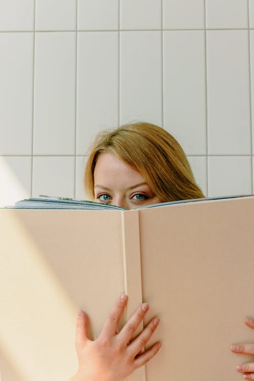 Woman Covering Her Face With Book