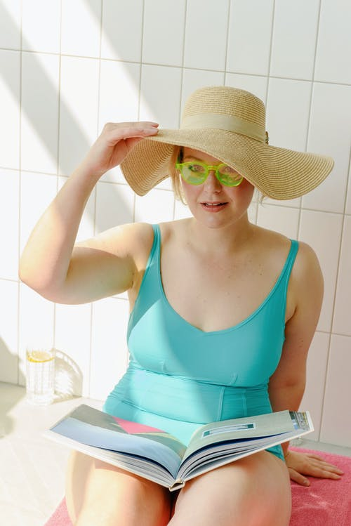 Woman in Teal Swimsuit Holding Her Sun Hat