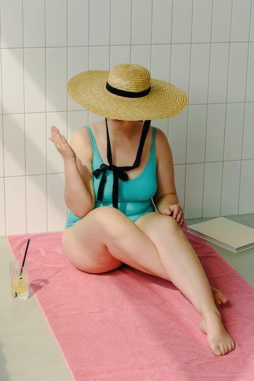 Woman in Teal Swimwear Sitting on a Towel