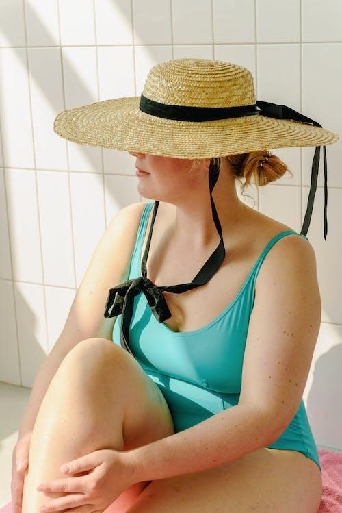 Woman in Teal Swimwear and Sun Hat