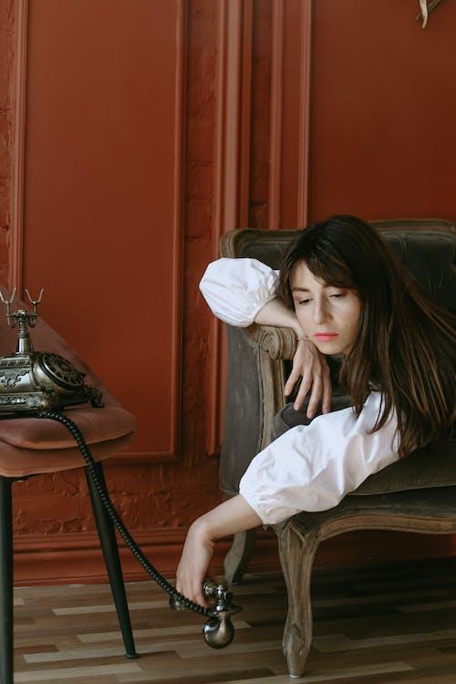 Woman Lying on Sofa while Holding Telephone