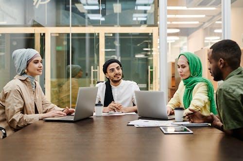 Woman in Green Hijab Using Macbook