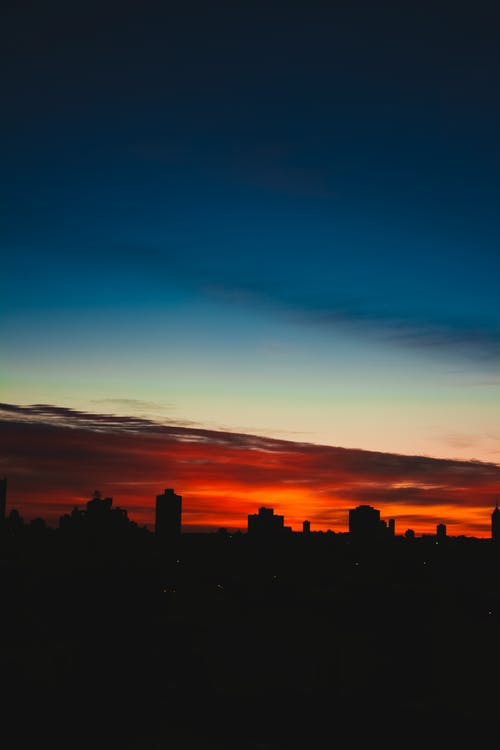 Scenic view of house silhouettes under red and blue cloudy sky in town at night