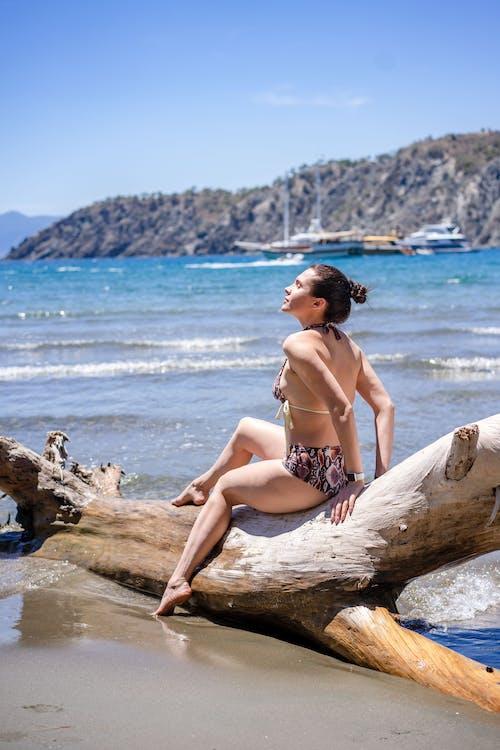 Side view of young female in swimwear sitting on log on sandy beach near rippling sea near rocky coast on sunny summer day