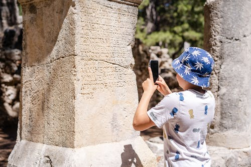 Boy taking photo of old monument
