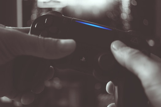 Black And White Photo Of Man Holding Sony Ps4 Wireless Controller