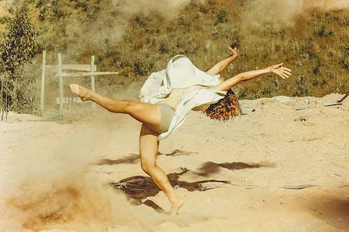 Woman Wearing White Dress Dancing on Brown Sand