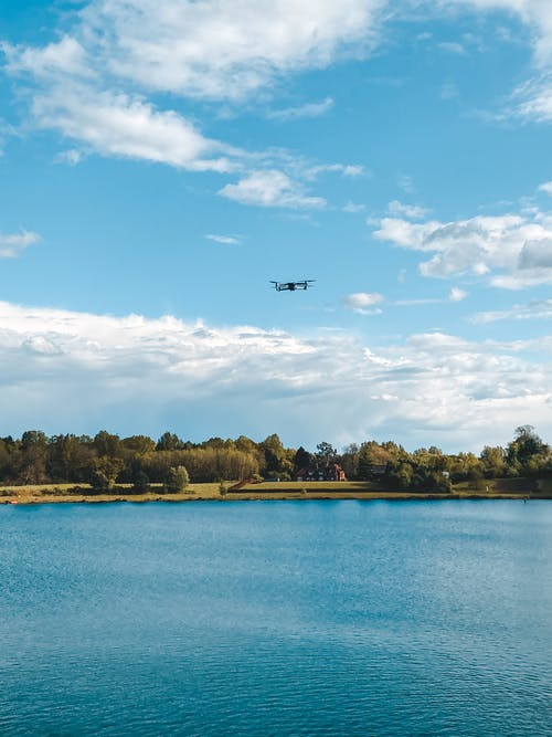 Black Airplane Flying over the Lake