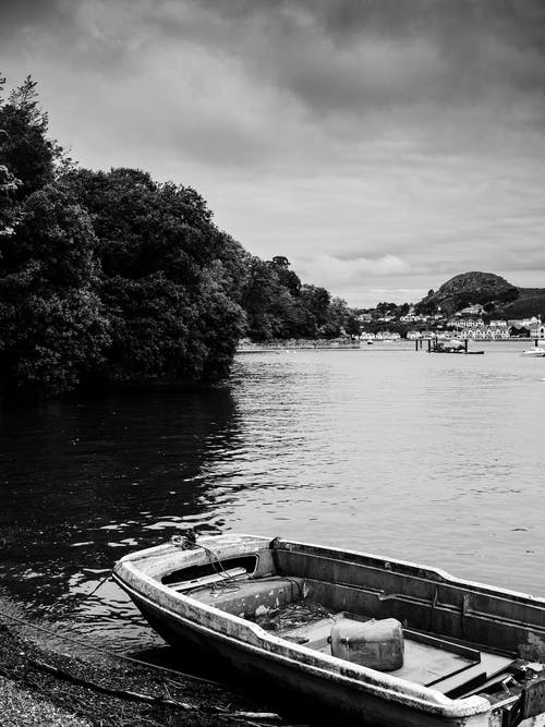 Grayscale Photo of Boat on Lake