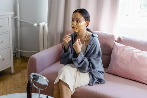 Young Asian female with facial mask applied on face sitting on couch near table with mirror during skincare routine at home