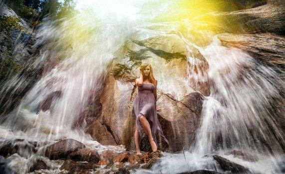 Woman in Gray Strapless Long Dress Standing Under Waterfalls