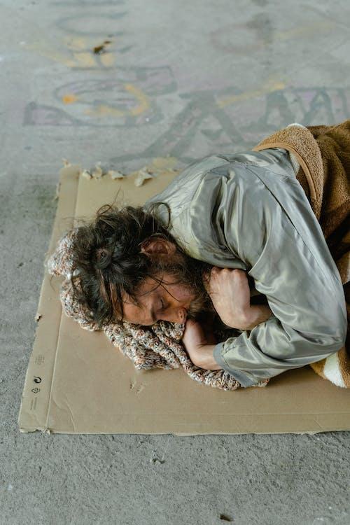Man in Gray Long Sleeve Shirt Lying on Brown Cardboard Box