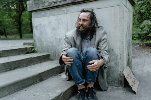 Man in Gray Coat Sitting on Concrete Stairs