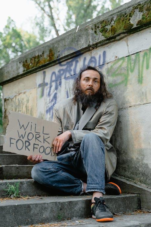 Man Holding a Cardboard Banner