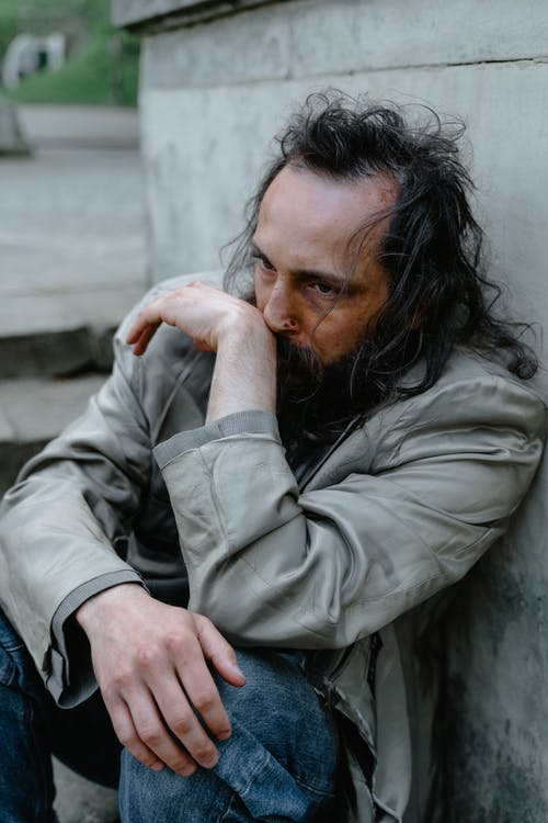 Man in Gray Jacket and Blue Denim Jeans Sitting on Gray Concrete Bench