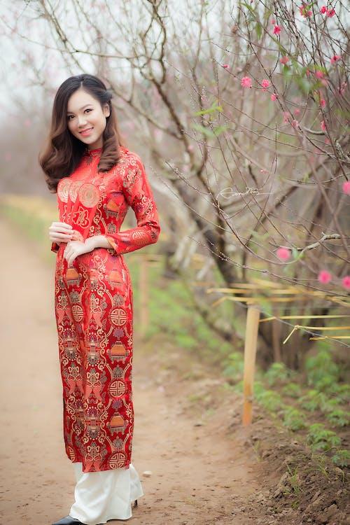 Mujer En Vestido Rojo De Manga Larga Con Cuello Redondo Cerca De árbol Desnudo
