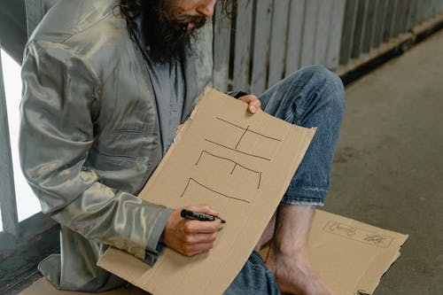 Person Writing on Cardboard
