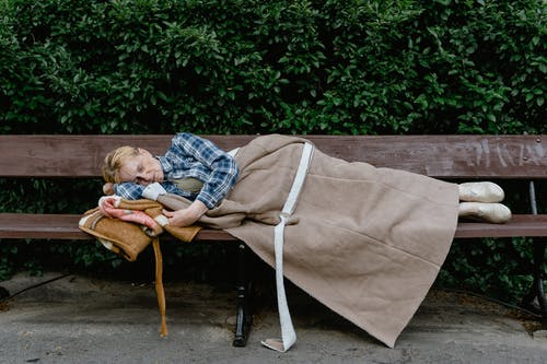 Woman Sleeping on a Wooden Bench