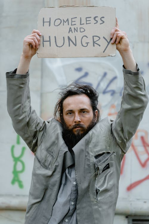 Man in Gray Jacket Holding a Brown Cardboard Poster