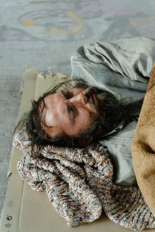 A Male Beggar Sleeping on the Street