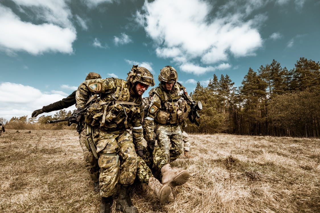 2 Men in Camouflage Uniform Standing on Green Grass Field Under Cloudy Sky