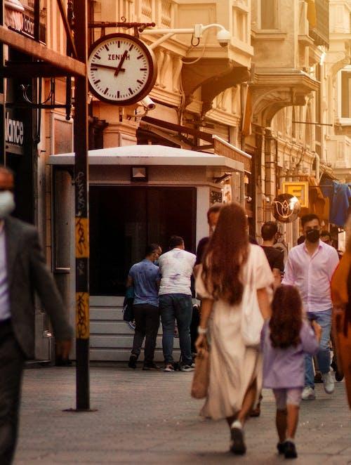 Crowd walking near clock on street