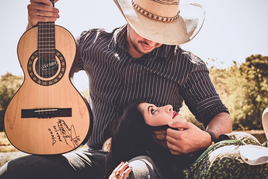 Woman In Green Top With Man In Black Long-sleeved Shirt Holding Autographed Brown Guitar