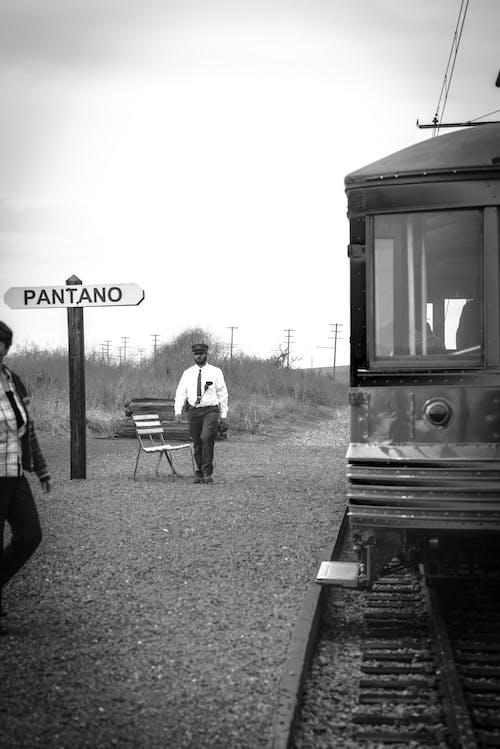 Grayscale Photo of Man Walking Near Train