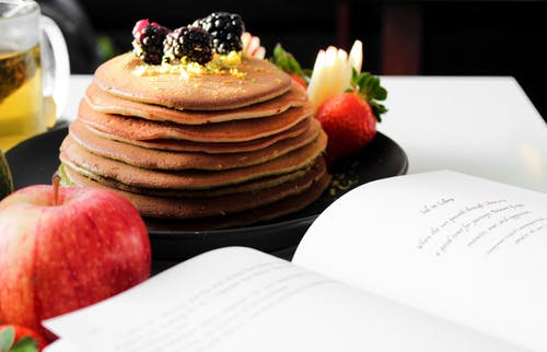 Delicious appetizing pancakes on black plate with blackberries on top and apple near opened book