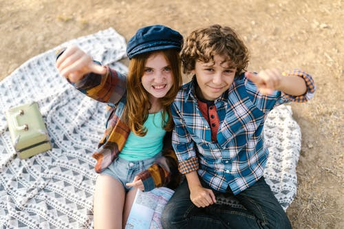 Overhead Shot of Two Teens Sitting on Picnic Blanket while Looking at Camera