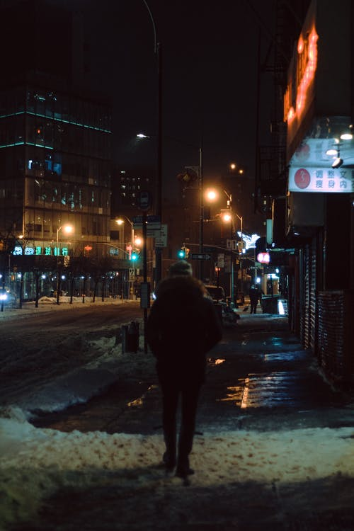 Back view of unrecognizable person in warm clothes walking on snowy street in city in evening time