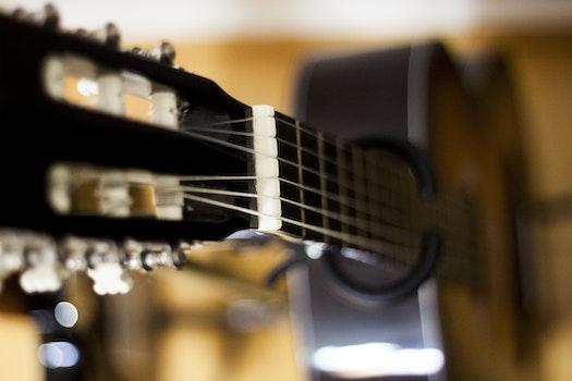 Selective Focus Photo of Black Classical Guitar