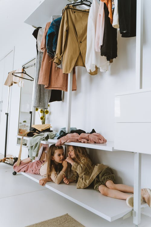 Girls Playing Hide and Seek Under the Shelves