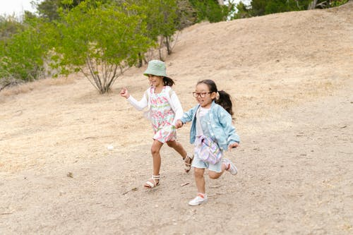 Two Girls Holding Hands While Running