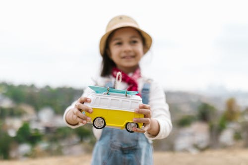A Plastic Toy Van Held by a Beautiful Girl