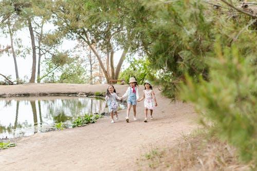 Three Children Holding Hands While Walking