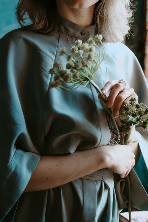 Woman in Blue Dress Holding White Flowers